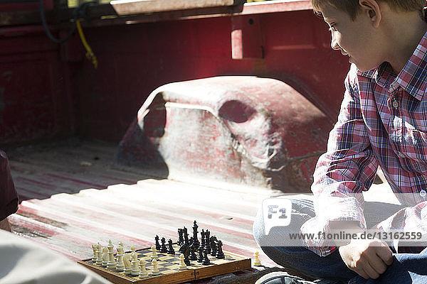 Junge mit gekreuzten Beinen auf dem Rücksitz eines Pickup-Trucks beim Schachspielen