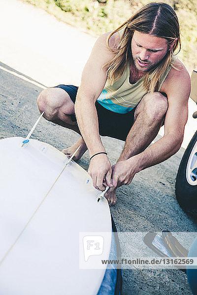 Junger Mann arbeitet auf einem Surfbrett