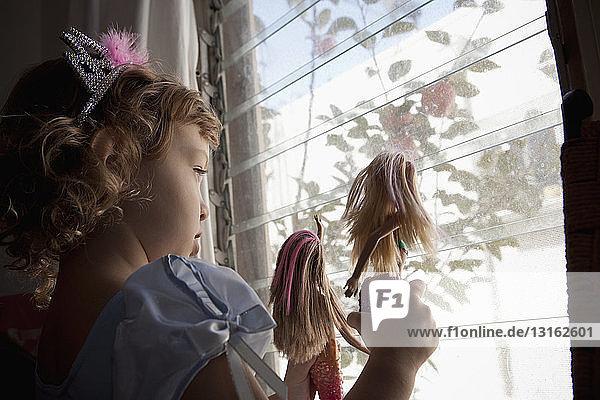 Weibliches Kleinkind schaut aus dem Fenster und hält Puppen hoch