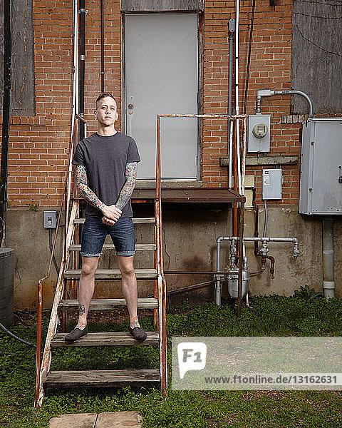 Porträt eines jungen tätowierten Mannes auf einer Treppe stehend