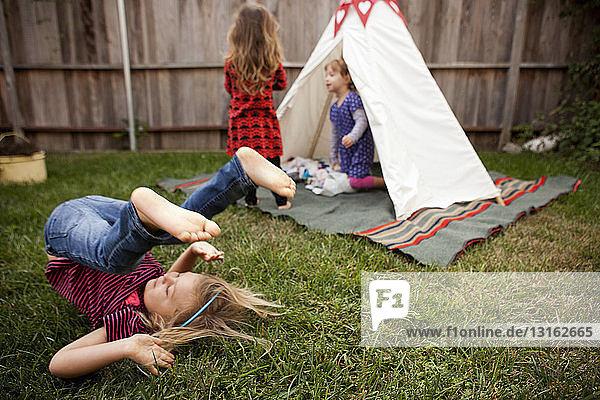 Drei junge Mädchen spielen im Garten
