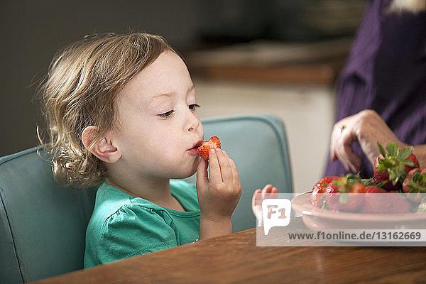 Mädchen sitzt und isst eine Schale Erdbeeren
