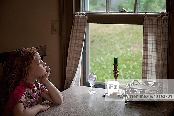 Nachdenkliches Mädchen schaut durch offenes Fenster