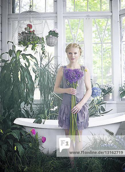Junge Frau mit Blumenstrauss in der Hand,  steht im Badezimmer voller Pflanzen