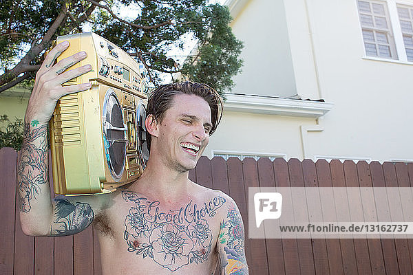 Young man with tattoos carrying boom box