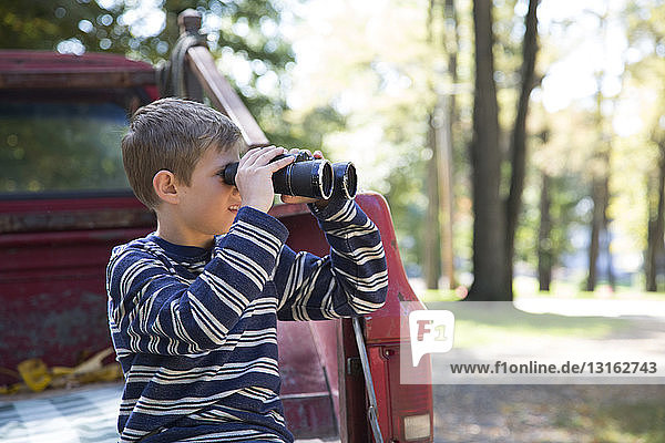 Boy leaning against pickup truck looking through binoculars in woods