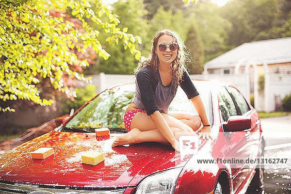 Junge Frau auf Motorhaube sitzend  Porträt