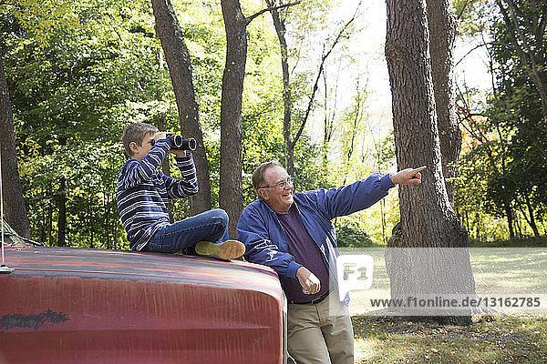 Senioren und Enkel beim Zeigen und Benutzen von Ferngläsern in Wäldern