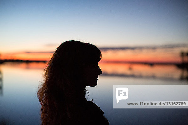 Side view of young woman in silhouette looking out over water