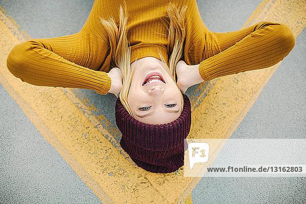 Überkopfporträt einer jungen Frau  die auf einer gelben Straßenmarkierung liegt