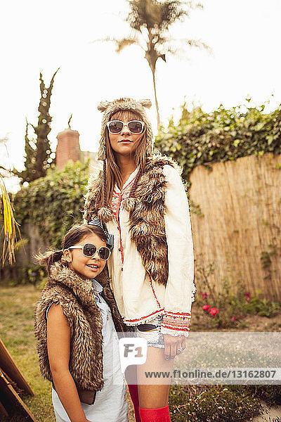 Mutter und Tochter tragen pelzige Körperwärmer und Sonnenbrillen