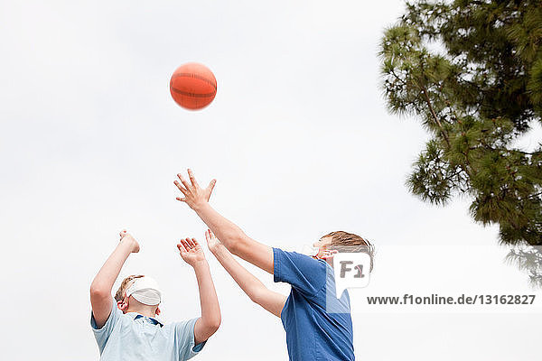 Two boys wearing dust masks playing basketball