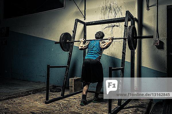 Gewichtheberin in dunkler Turnhalle