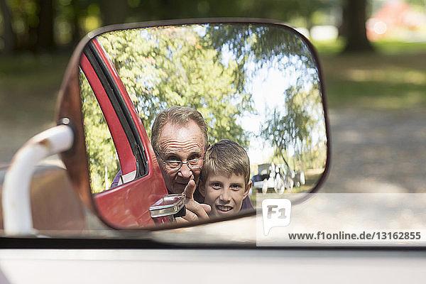 Älterer Mann und Enkel im Außenspiegel des Lastwagens reflektiert