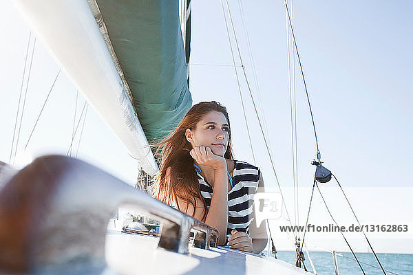 Young woman on yacht wearing striped top