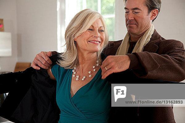 Mann hilft Frau beim Anziehen des Mantels