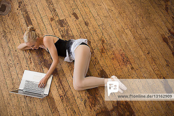 Balletttänzer mit Laptop auf Holzboden liegend