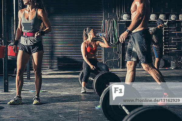 Frau sitzt auf Hantel und trinkt Wasser im Fitnessstudio