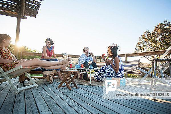 Junge Freunde sitzen zusammen auf dem Balkon