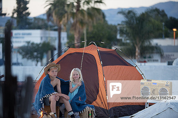 Brother and sister with boom box sitting next to orange colour tent wrapped in blanket