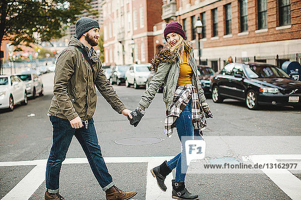 Young couple holding hands crossing city street