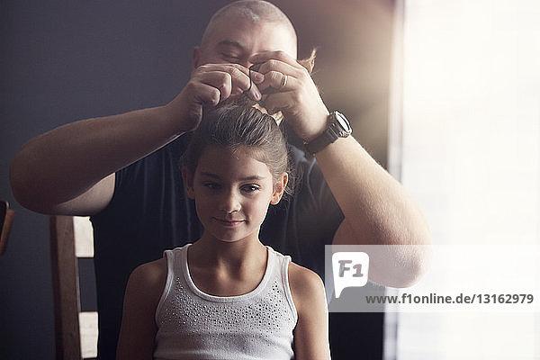 Vater macht seiner Tochter die Haare