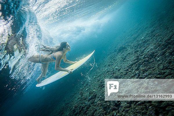 Surfer tauchen unter der Welle im Wasser