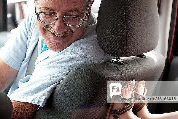 Großvater schaut sich auf der Rücksitzlehne im Auto nach Kinderfüßen um