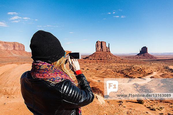 Mittlere erwachsene Frau  die Monument Valley auf einem Smartphone fotografiert  Utah  USA