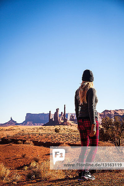 Rear view of mid adult woman looking out at Monument Valley  Utah  USA
