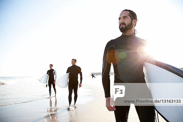 Drei Surfer am Strand