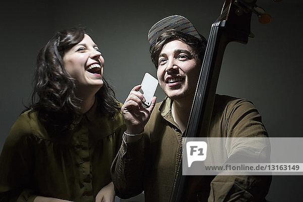 Junge Musiker mit Kontrabass und Smartphone  lachend Junge Musiker mit Kontrabass und Smartphone, lachend