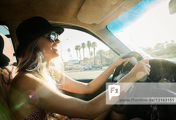 Junge Frau fährt Auto im Sonnenlicht und lächelt