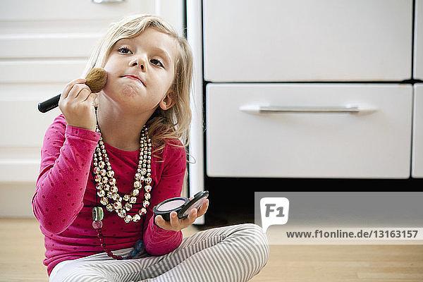 Junges Mädchen sitzt mit Make-up auf dem Küchenboden