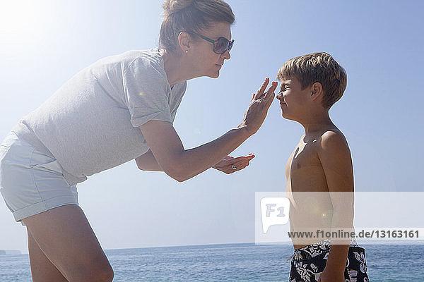 Mutter trägt Sonnenschutz auf Sohn auf
