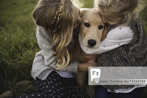 Two young girls hugging pet dog  outdoors