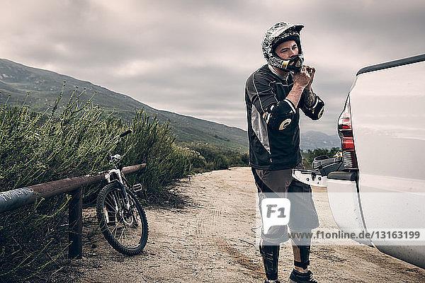 Downhill-Mountainbiker setzen Helm auf