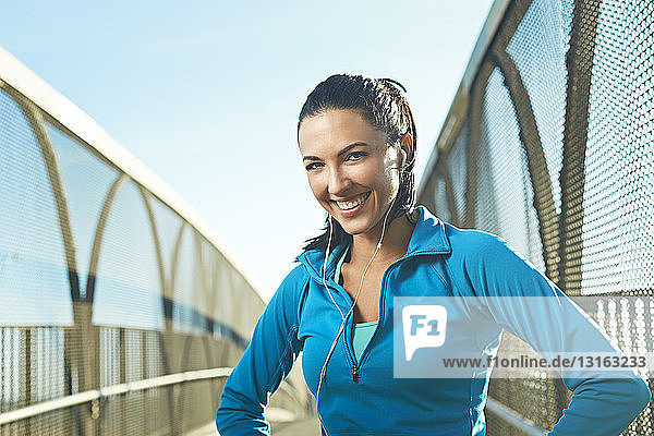 Mid adult woman wearing sports clothes standing on bridge