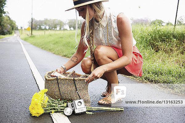 Junge Frau hockt am Straßenrand