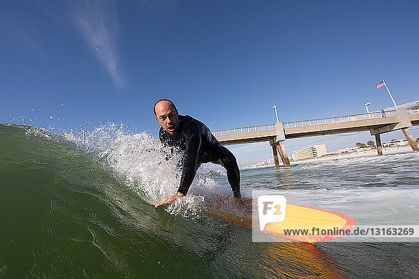 Mid adult man surfing on yellow surfboard next to bridge  Los Angeles  California  USA
