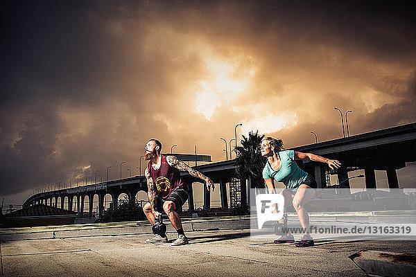 Mann und Frau trainieren mit Kettlebells auf dem Dach der Turnhalle