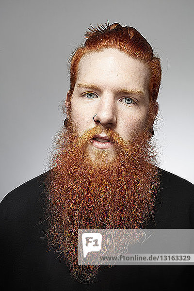 Studio portrait of staring young man with red hair and overgrown beard