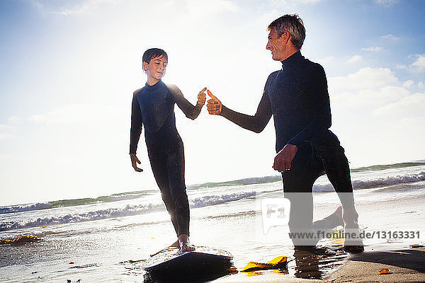 Father and son with surfboard on beach  Encinitas  California  USA