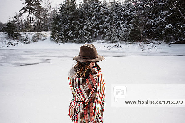 Portrait of woman wrapped in blanket in snow covered landscape  Omemee Ontario Canada