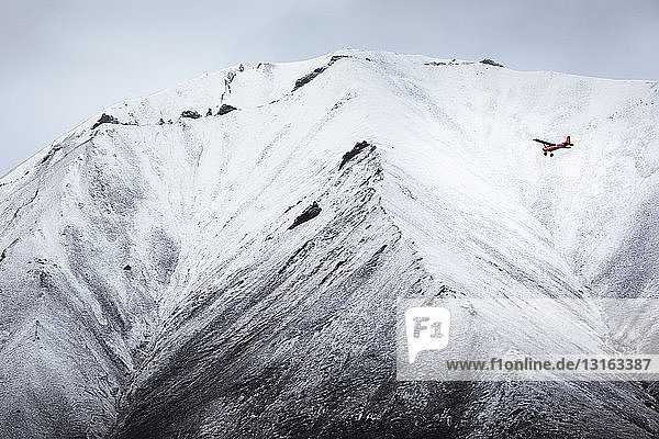 Airplane flying in front of snow covered mountain  Wrangell St. Elias  Alaska  USA