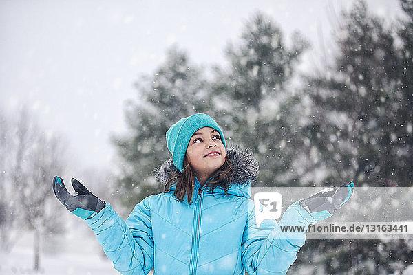 Mädchen mit türkisfarbener Strickmütze und -mantel  die Arme erhoben  die Hände nach Schnee streckend  lächelnd aufblickend