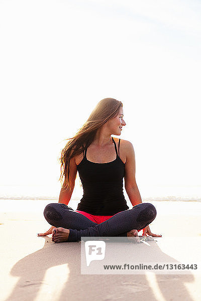 Woman in yoga pose on beach