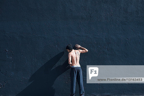 Barchested man leaning against a wall