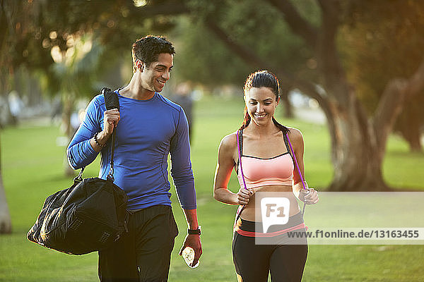 Man and woman wearing sports clothes walking through park