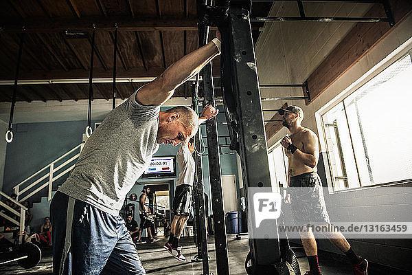 Männer beim Training an der Stange in der Turnhalle